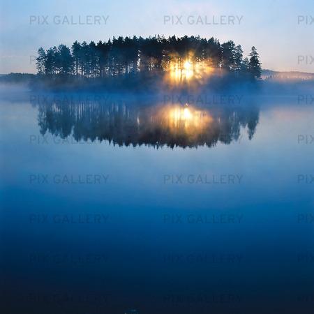 Soluppgång vid stilla insjö, Värmland