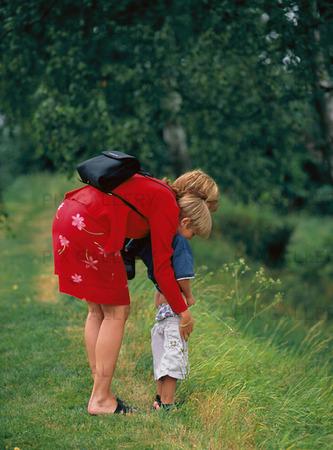 Mor med pojke som är kissnödig