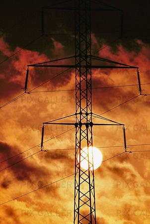 Solen bakom kraftledningsstolpe