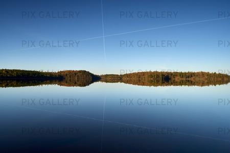 Spegling av linjer i stilla insjö