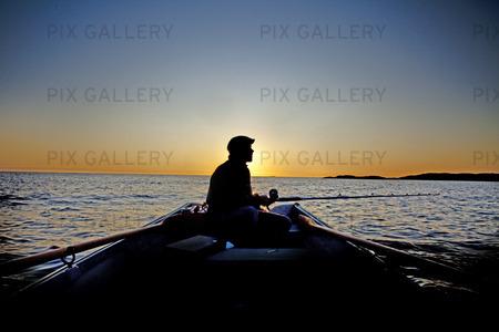 Fritidsfiske från roddbåt i solnedgång