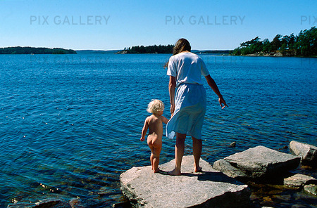 Barn med mamma vid havet