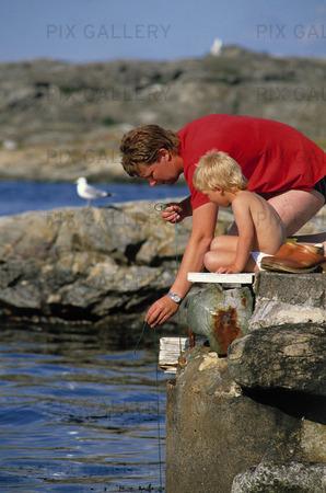 Man och barn fiskar krabbor