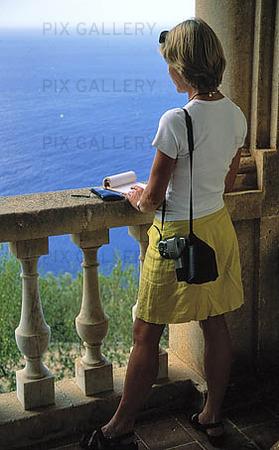 Kvinna tecknar vid Medelhavet
