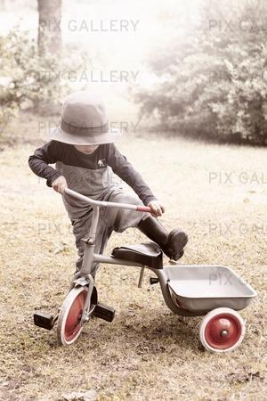 Liten pojke med trehjuling