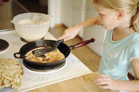Flicka steker pannkakor