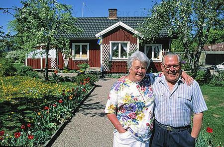 Äldre par framför villa