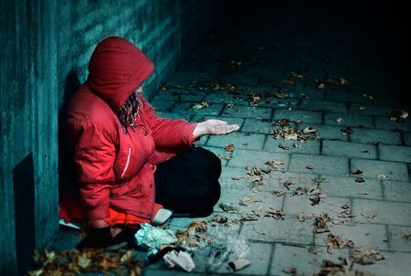 A woman sitting against a brick building
