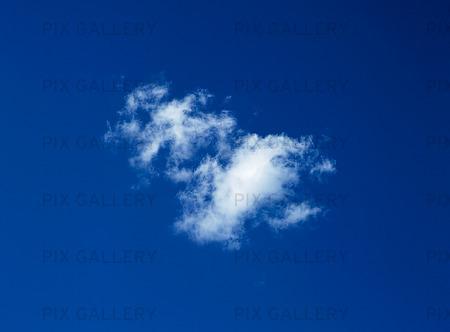 Ensamt moln på blå himmel