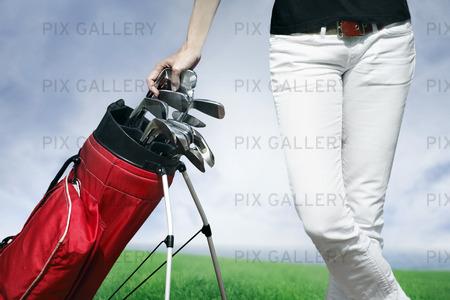 Women standing by golf bag full of sticks