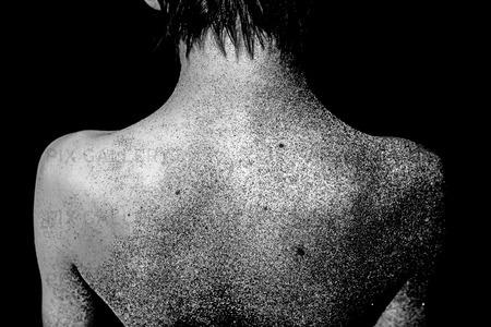 Naken pojke med sand på ryggen