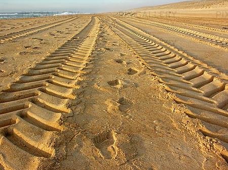 Däckspår på sandstrand