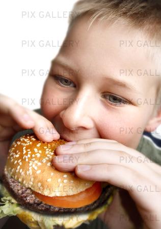 Ung pojke äta ostburgare