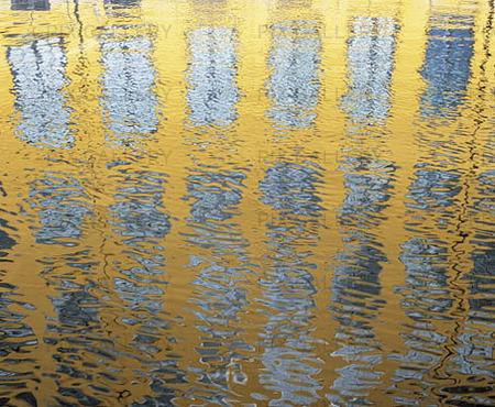Spegling av husfasad i vattenyta