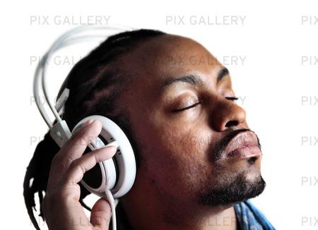 Man lyssnar på hörlurar med slutna ögon
