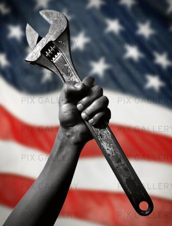 Arbetare med skiftnyckel med USAs flagga i bakgrunden