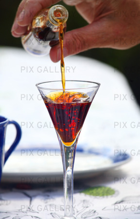 Likör som hälls i ett glas med is