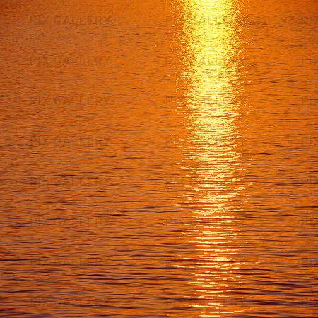 Solnedgång speglas i vattenyta