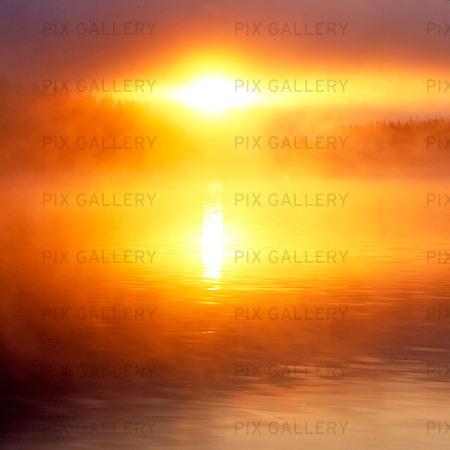 Soluppgång i dimma vid sjö