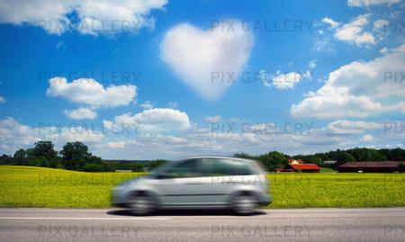 Bil på landsväg med hjärtformat moln på himlen