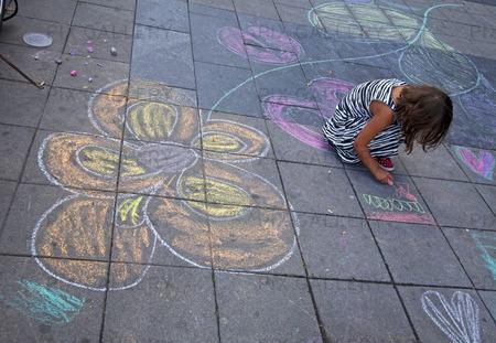 Flicka som ritar på gatan