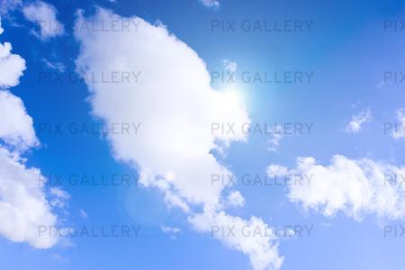 Sol, vita moln och blå himmel