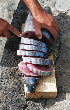 Fiskare skär fisk i bitar