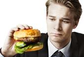 Affärsman äter hamburgare på jobbet