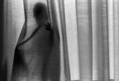 Människa bakom gardin