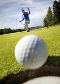 Golfbollen i rullning i hålet