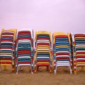 Solstolar på sandstrand