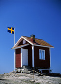Svensk flagga vid stuga