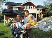 Tvåbarnsfamilj framför villa