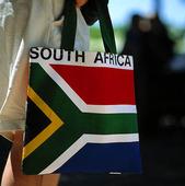 Turist med Sydafrikas flagga på väska