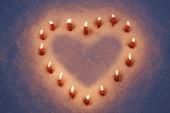 Stearinljus i snö med form av ett hjärta