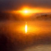 Soluppgång i morgondimma vid sjö