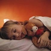 Flicka som sover med nallebjörn