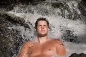 Man som badar i vattenfall