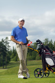 Man standing by golf bag full of sticks