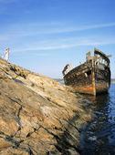 Flicka vid gammalt båtvrak