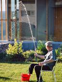 Man som vattnar i trädgård med foten i hink