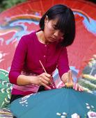Kvinna tillverkar parasoll, Thailand