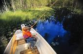 Pojke som fiskar från eka