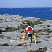 Far med barn på klippor