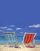 Två solstolar på stranden