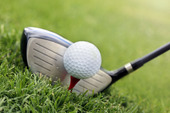 Golfklubba och boll i gräset