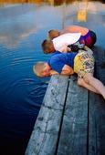 Barn som fiskar krabbor på brygga