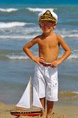 Pojke med segelbåt på strand