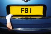 FBI-skylt på bil med en arm som hänger ut från bagaget