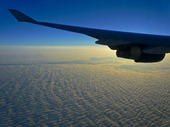 Airplane wing flying over clouds at sunrise